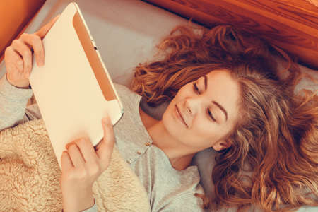ebook: Lazy young woman using computer tablet browsing internet. Girl laying in bed under blanket and holding ebook. Technology leisure. Instagram filter. Stock Photo