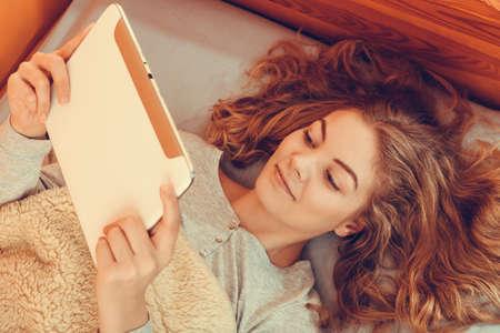 perezoso: Mujer joven perezoso que usa la tableta del ordenador de navegación por Internet. Muchacha que pone en la cama bajo la manta y la celebración de libro electrónico. Ocio Tecnología. Filtro de Instagram. Foto de archivo