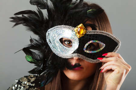 to conceal: Holidays, people and celebration concept. Closeup woman face with carnival venetian mask on gray background.