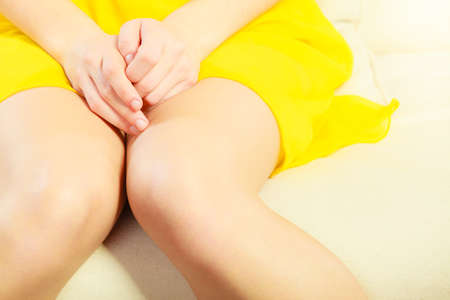 mujer sentada: mujer joven de cerca sentado en el sofá, sólo las piernas y la vuelta está mostrando, ella es tímida Foto de archivo