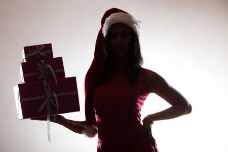 giver: Christmas time. Attractive lovely mixed race woman in christmas santa claus cap hat with presents boxes gifts. Helping and giving concept. Stock Photo