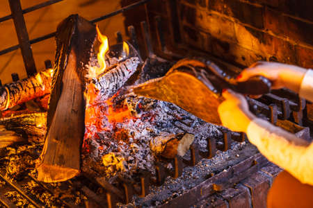 Closeup of human hands at fireplace making fire with bellows. Person heating warming up and relaxing. Winter at home.