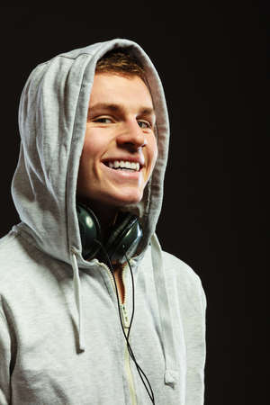 young boy smiling: Smiling handsome hooded man with headphones listening to music sideview dark background