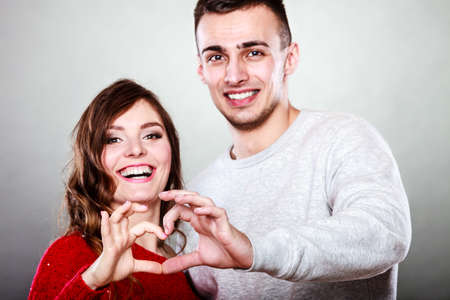 couple in love: Love concept. Closeup Smiling woman and man forming heart shape with their fingers hands