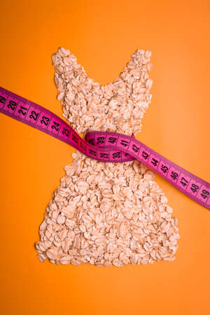 waist down: Dieting healthy eating slim down concept. Female dress shape made from oatmeal with measuring tape around thin waist on orange Stock Photo