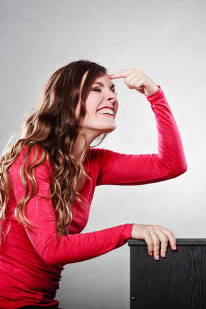 mocking: Woman gesturing with finger on her head. Are you crazy? Girl mocking laughing at somebody.