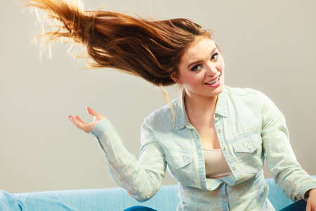 windblown: Young people happiness concept. Fashionable girl with long hair blowing