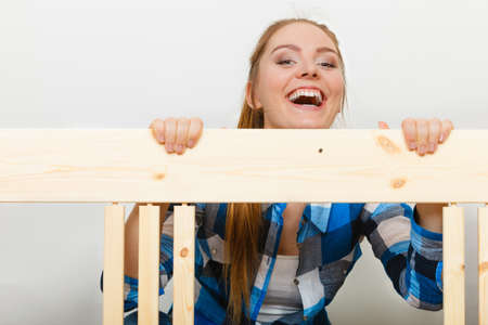 enthusiast: Happy smiling woman assembling wooden furniture. DIY enthusiast. Young girl doing home improvement.