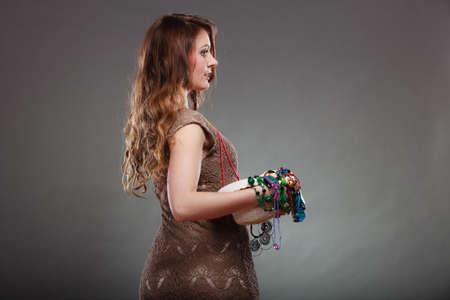 plentiful: Pretty young woman holding hat and many plentiful of precious jewelry necklaces beads. Portrait of gorgeous fashion girl in studio on gray. Stock Photo