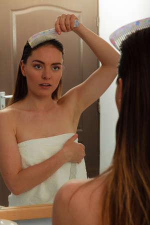 taking shower: Woman combing wet hair after taking shower. Girl with wet hair looking in mirror. Bathroom hygiene.