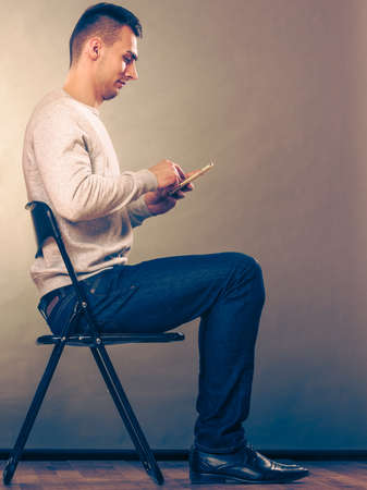 absorbed: Man using mobile phone sitting in chair. Absorbed male texting messages. New technology.