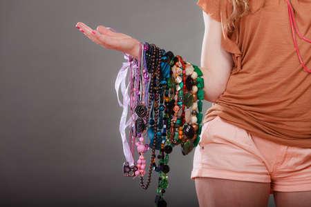 plentiful: Closeup of woman holding many plentiful of precious jewelry necklaces beads. Fashion girl in studio on gray.