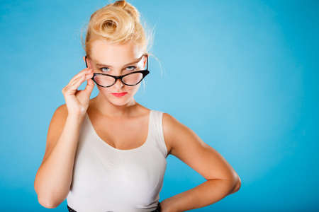 oculist: Optometrist, oculist and ophthalmologist concept. Young blonde retro pin up angry woman with eyeglasses on blue background in studio.