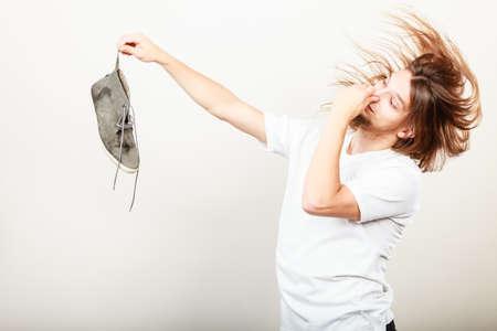 olfato: Joven hombre de largo cabello vistiendo la camiseta blanca que sostiene el zapato sucio sudor apestoso en uno dedos de la mano. hedor olor desagradable.