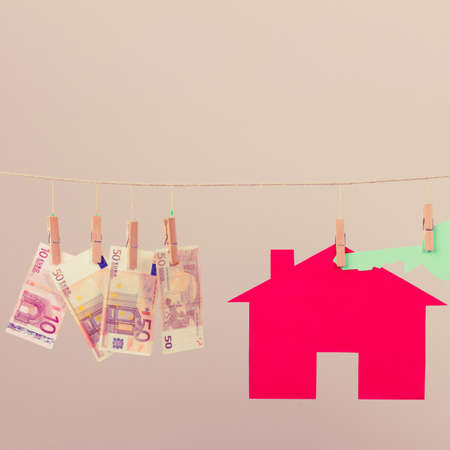laundry concept: Red house with green key and banknotes cash hang on laundry line. Selling and buying home concept.