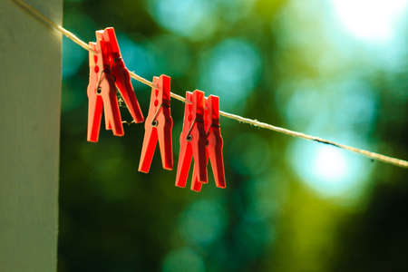clothes clips: Red clips for washing laundry clothes pegs on string rope outdoor. Housework concept.