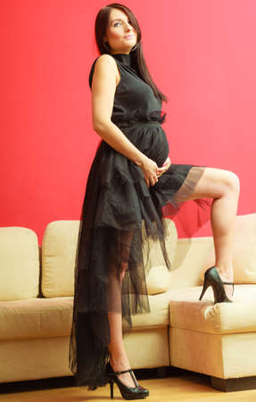 mothering: Stylish pretty girl in black evening dress. Pregnant woman preparing for event. Glamour look. Prospective mothering concept.
