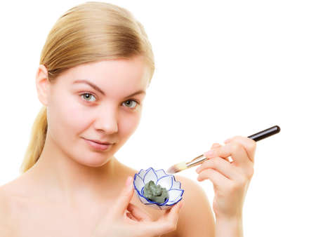 complexion: Skin care. Woman applying with brush clay mud mask on face isolated on white. Girl taking care of dry complexion. Beauty treatment.