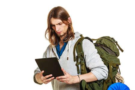 Backpacker man met behulp van de computer van de tablet browsen surfen op het internet. Jonge wandelaar backpacken. Moderne technologie.