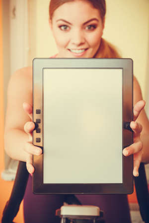 stationary bicycle: Active young woman working out on exercise bike stationary bicycle holding pc tablet computer with blank screen copyspace. Sporty girl training at home. Fitness and weight loss advertisement concept.