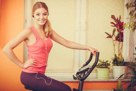 escucha activa: Active joven que se resuelve en la bici de ejercicio en bicicleta estacionaria. Formación Muchacha deportiva en casa escuchando música. Fitness y concepto de pérdida de peso.