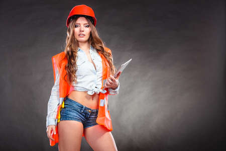 Sexy alluring woman structural engineer wearing helmet holding tablet computer. Strong girl feminist working in man profession. Independent female.