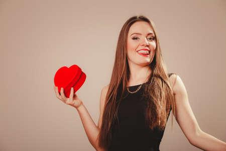 ragazza innamorata: L'amore e il concetto di aiuto di carit�. Giovane bellezza felice lunghi ragazza donna dai capelli in abito nero holding regalo casella di cuore in studio.