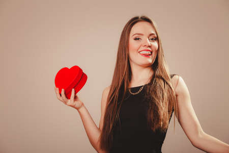 funny love: Love help and charity concept. Young beauty happy long haired woman girl in black dress holding heart box gift in studio.