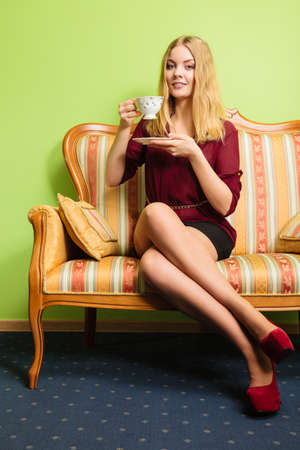 energizing: Fashionable woman drinking cup of coffee sitting on vintage sofa. Young girl with hot energizing beverage stay awake. Caffeine energy.