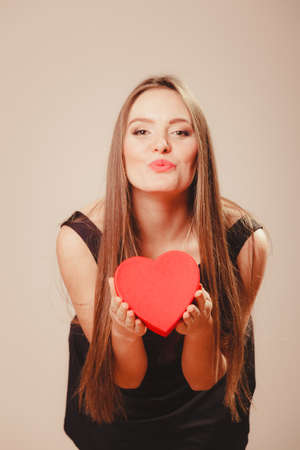 mujer enamorada: Love help and charity concept. Young beauty cute long haired woman girl in black dress blowing kiss holding heart box gift present in studio. Foto de archivo