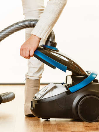 hygenic: Young woman opening vacuum cleaner on white. Houseworking in home. Stock Photo