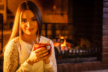 tea hot drink: Woman drinking cup of coffee relaxing at fireplace. Young girl with hot beverage heating warming up. Winter at home. Stock Photo