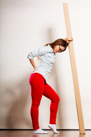 carrying heavy: Unhappy tired woman moving into new apartment house carrying heavy carton box with furniture. Young girl arranging interior and unpacking. Female having backache pain. Stock Photo