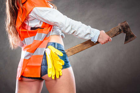 axe girl: Closeup of woman wearing safety workwear holding axe chopper. Strong girl feminist working in man profession. Independent female.