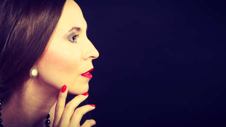 subtlety: Fashion beauty and elegance concept. Woman retro style face profile. Elegant lady hair styling red lips on black