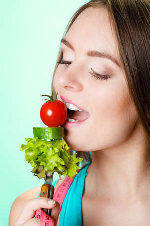 Eating, dieting, slimming and healthcare concept. Young fit woman with measuring tape on neck holding and biting fresh mixed vegetables. Studio shot on blue background.
