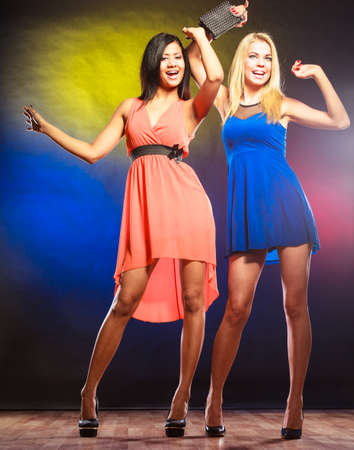 dancing woman: Party, celabration, carnival. Two attractive funny dancing women in dresses on colorful background in studio. Stock Photo