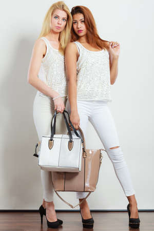 spiked: Elegant outfit. Female fashion. Two women blonde and mixed race in fashionable clothes high heels with bags handbags.