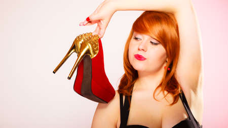 high heeled shoes: Shopaholic, fashion and women style. Shopping time. Young red haired female holding high heeled shoes in hands on pink background. Studio shot. Stock Photo
