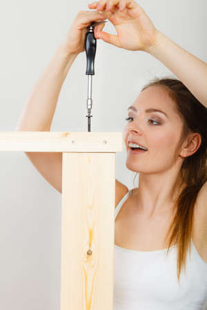woman desk: Woman assembling wooden furniture using screwdriver. DIY enthusiast. Young girl doing home improvement.