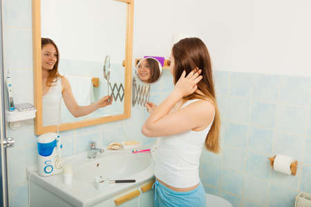 purity: Young girl woman without makeup in bathroom looking in mirror. Natural beauty. Purity.