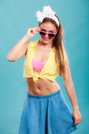 hairband: Portrait of happy smiling pretty pin up girl with hairband bow wearing sunglasses. Attractive gorgeous young retro woman posing in studio on blue background.