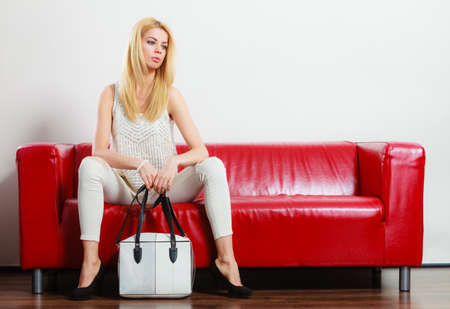 spiked: Elegant outfit. Female fashion. Blonde woman wearing fashionable clothes high heels with bag handbag sitting on red couch. Stock Photo