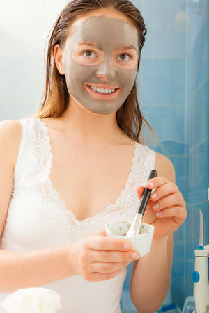 mud woman: Beauty procedures skin care concept. Young woman applying facial gray mud clay mask to her face in bathroom