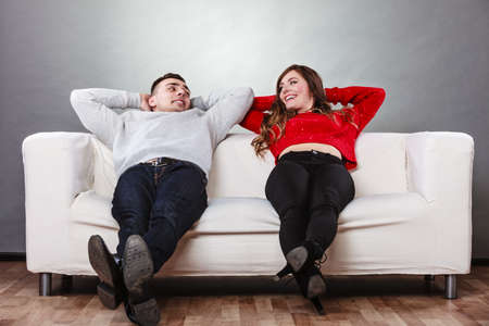 Happy, smiling young couple relaxing on couch at home. Calm, carefree man and woman resting with arms behind head looking at each other. Healthy relationship. Stock Photo