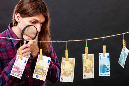 verify: Currency exchange concept. Man worker check verify money cash. Payment hang on laundry line. Guy with loupe magnifying glass Stock Photo