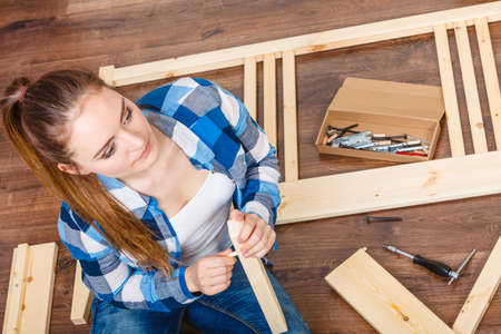 woman desk: Woman girl with screwdriver and nails assembling furniture. DIY home improvement.