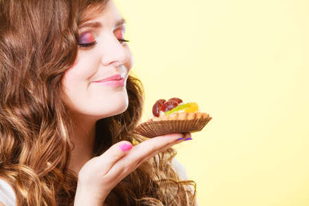indulging: Bakery sweet food indulging and people concept. Cute attractive woman closed eyes holds cake cupcake in hand smelling yellow background