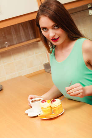 gluttony: Woman with cup of coffee forking delicious gourmet sweet cream cake cupcake and orange. Glutton girl sitting in kitchen with hot beverage having breakfast. Appetite and gluttony concept. Stock Photo