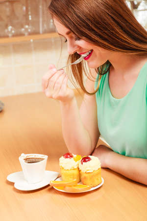 glutton: Woman with cup of coffee eating delicious gourmet sweet cream cake cupcake and orange. Glutton girl sitting in kitchen with hot beverage having breakfast. Appetite and gluttony concept. Stock Photo
